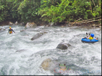 guide waiting to receive a kid in the rapids blue river tubing rincon de la vieja