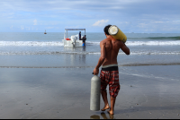 Snorkel instructor helping carry diving tanks