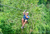 a man zip lining sitting down los canones canopy tour la fortuna
