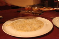 grating cheese on black truffle cream ravioli 