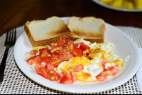 scrambled eggs topped with fresh tomatoe served with a toast