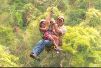 young girl riding with a guide tizati zip line rincon de la vieja
