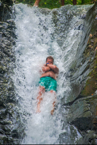 man sliding on uvita waterfall waterfall tour manuel antonio