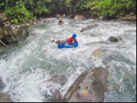 lady tubing on the rocky rapids of blue river rincon de la vieja