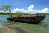 An old barge rusts in the salt water off the coast of Playa Negra