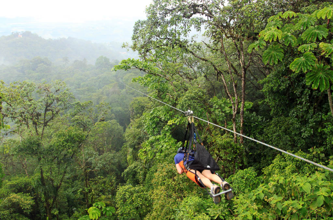 A visitor rides a zip line on the Superman de Osa tour